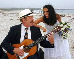 Terrence Farrell plays guitar at a beach wedding